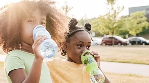 Girls drinking from water bottle
